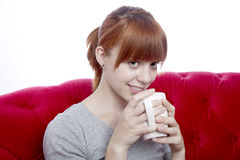 Young girl on red sofa with cup of tea Royalty Free Stock Photo