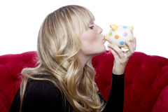 Young girl on red sofa kisses piggybank Royalty Free Stock Images