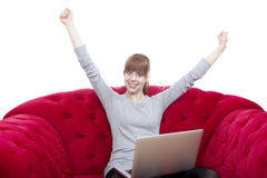 Young girl on red sofa raise arms in the air. Young beautiful red haired girl on red sofa raise arms in the air in front of white background Royalty Free Stock Images