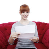 Young girl on red sofa reading a letter Royalty Free Stock Photos