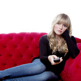Young girl on red sofa with remote control Royalty Free Stock Images