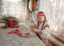 A young girl in a red suit collects Rowan berries on a thread. Russian girl makes red beads