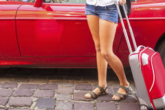 Young girl with red suitcase near the car. Travel concept Stock Photography