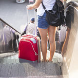 Young girl with the red suitcase standing on the escalator. Royalty Free Stock Image