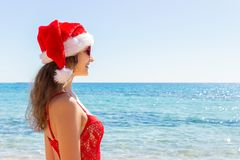 Young girl in red swimsuit and christmas hat on beach. copy space stock photo