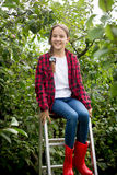 Young girl in red wellington boots  sitting on stepladder at gar Royalty Free Stock Image