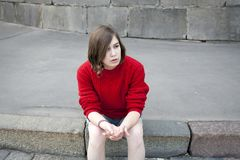 Young girl in a red wool sweater and jeans shorts is sitting on the steps Royalty Free Stock Image