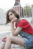 Young girl in a red wool sweater and jeans shorts is sitting on the steps Stock Photography