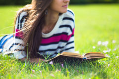 Young girl relax with book in summer park. Happy young teenager student of Caucasian ethnicity. Summer lifestyle concept Royalty Free Stock Photography