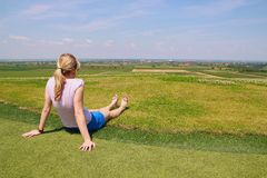 Young girl relax on grass. Young girl relax on golf terrain and enjoy in view royalty free stock photos