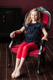 Young girl relaxing in armchair against brown wall Stock Photos