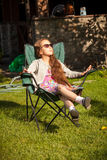 Young girl relaxing in armchair on grass at sunny day Royalty Free Stock Images