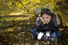 Young girl relaxing in autumn park Stock Photos