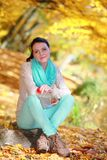 Young girl relaxing in autumnal park. Fall lifestyle concept. Royalty Free Stock Photos