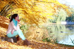 Young girl relaxing in autumnal park. Fall lifestyle concept. Royalty Free Stock Image