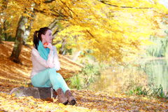 Young girl relaxing in autumnal park. Fall lifestyle concept. Stock Image
