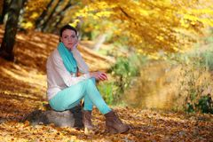Young girl relaxing in autumnal park. Fall lifestyle concept. Stock Photo