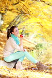 Young girl relaxing in autumnal park. Fall lifestyle concept. Royalty Free Stock Images