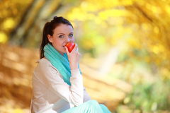 Young girl relaxing in autumnal park. Fall lifestyle concept. Royalty Free Stock Photography