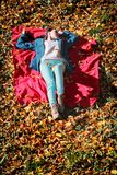 Young girl relaxing in autumnal park lying on red blanket Stock Photo