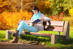 Young girl relaxing in autumnal park reading book Royalty Free Stock Image