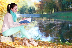 Young girl relaxing in autumnal park reading book Royalty Free Stock Photography