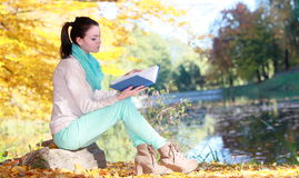 Young girl relaxing in autumnal park reading book Stock Photos