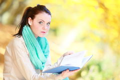 Young girl relaxing in autumnal park reading book Royalty Free Stock Images