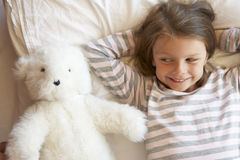 Young Girl Relaxing In Bed With Toy Stock Photography