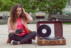 Young girl relaxing in city park, and listening music with headphones and a portable stereo vinyl record system Royalty Free Stock Image