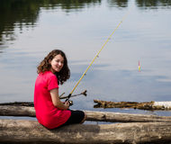 Young girl relaxing while fishing the lake Stock Photos