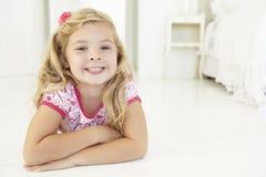 Young Girl Relaxing On Floor In Bedroom Stock Images
