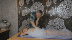 Young girl relaxing with foam massage in the Turkish bath. The camera moving from left to right. The girl laying the head on the hands on the table in the stock footage