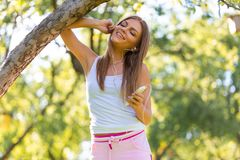 Young woman relaxing after jogging. She is using her smartphone and listening to music outdoor in summer time. royalty free stock photography