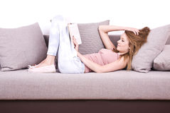 Young girl relaxing and reading a book Stock Photos