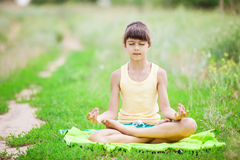 Young girl relaxing while sitting in lotus position. Stock Image