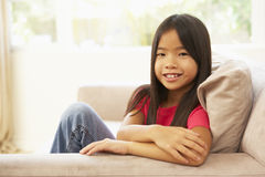 Young Girl Relaxing On Sofa At Home Stock Photography