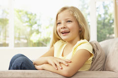 Young Girl Relaxing On Sofa At Home Royalty Free Stock Photo