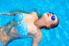 Young girl relaxing in summer pool Stock Photography