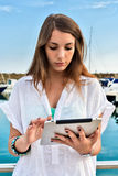Young girl relaxing with tablet at the dock Stock Photography