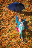 Young girl relaxing with umbrella in autumnal park Stock Photo