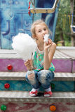 Young girl relishing a stick of candy floss Stock Photos