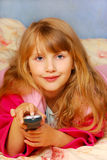 Young girl with remote control in hand. Young girl with remote control lying  on the bed Royalty Free Stock Images