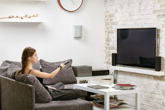 Young girl with remote control in hand, sitting on a sofa and wa. Tches TV Stock Photos
