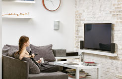 Young girl with remote control in hand, sitting on a sofa and wa. Tches TV Stock Photography