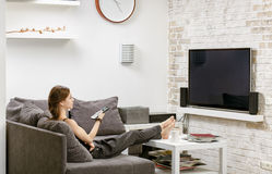 Young girl with remote control in hand, sitting on a sofa and wa. Tches TV Stock Photo