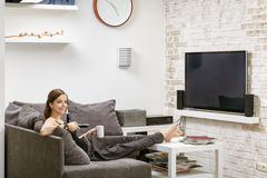 Young girl with remote control in hand, sitting on a sofa and wa. Tches TV Royalty Free Stock Image