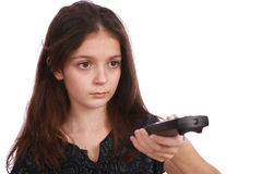 Young girl with remote control. Studio shot of a young girl with a remote control on a white background Royalty Free Stock Images