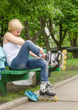 Young girl removing her rollerblades Royalty Free Stock Photo