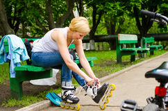 Young girl removing her rollerblades Royalty Free Stock Images